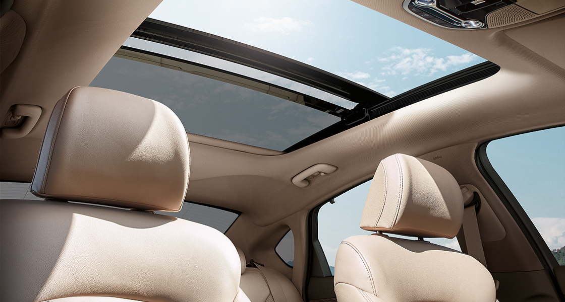 Low view of dark brown interior with sunroof opened on a clear day