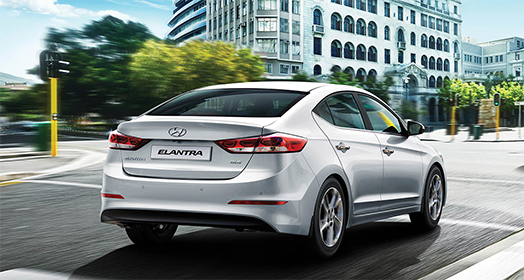 Side rear view of silver Elantra driving on the road in the city