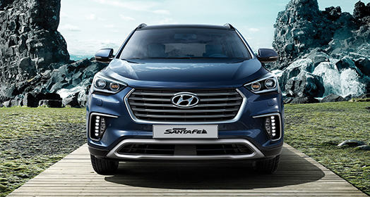 Front view of navy Grand Santafe parked with mountain background
