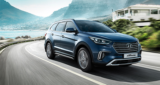 Side front view of navy Grand Santafe driving fast on the mountain side road