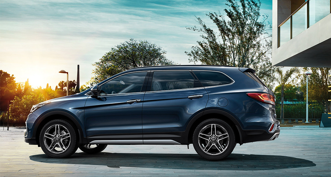 Side view of navy Grand Santafe with sunset