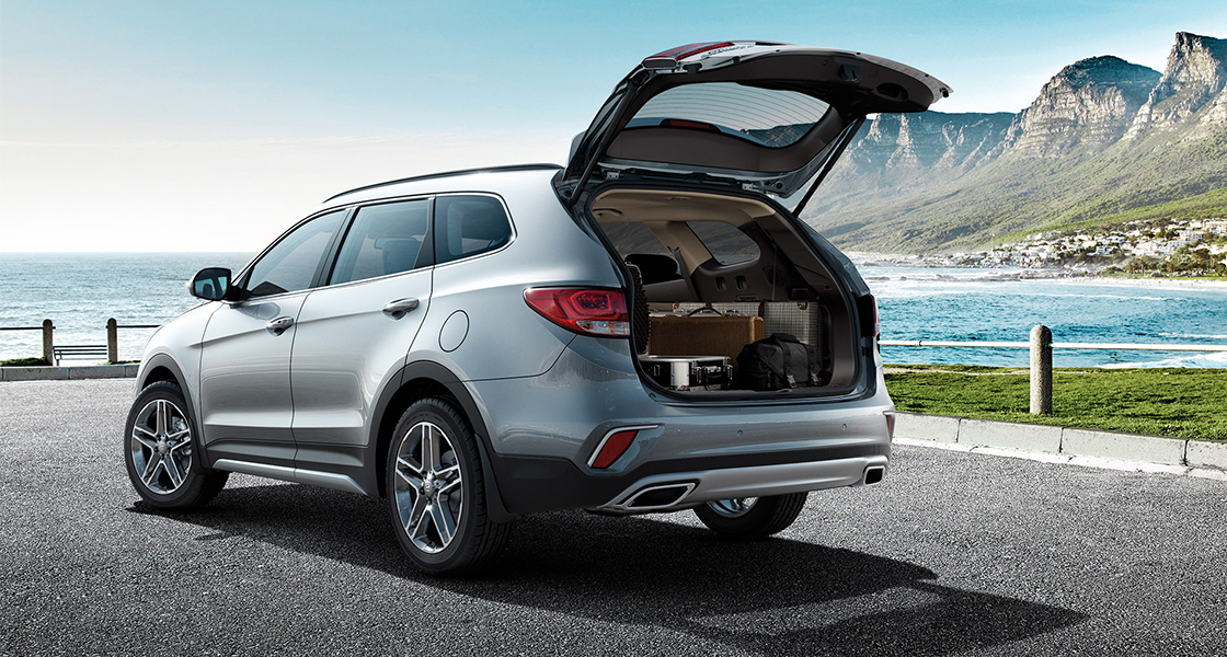 Side rear view of silver Grand Santafe with trunk door opened