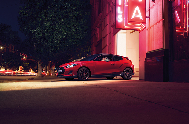 Right side view of red Veloster that opened trunk parked on the road.